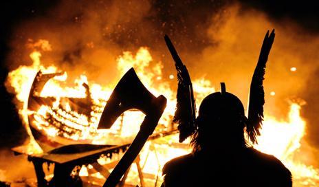 Man dressed up as viking at boat burning