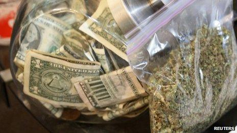 A bag of marijuana being prepared for sale sits next to a money jar in Northglenn, Colorado, on 31 December 2013