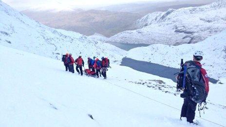 Aberglaslyn Mountain Rescue Team move the man down the mountain