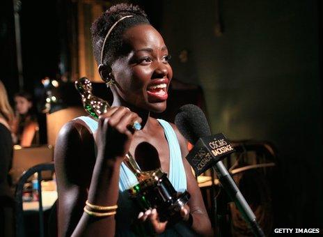 Lupita Nyong'o holding an Oscar