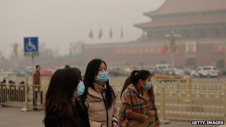 Three women in facemasks in China in front of a temple