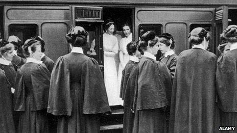 Nurses board a train In London to go to the continent