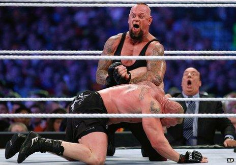 The Undertaker, top, and Brock Lesnar wrestle during Wrestlemania 30