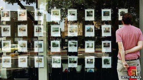 A man looks in a London estate agents window