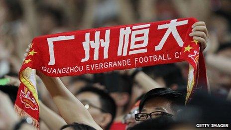 A fan holds up a Guangzhou Evergrande banner