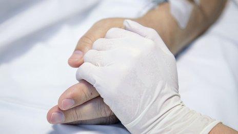 Nurse holding a patient's hand