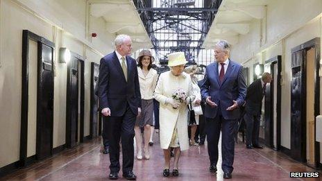 Queen Elizabeth (C) walks with Northern Ireland's First Minister Peter Robinson (R) and deputy First Minister Martin McGuinness on a visit to Crumlin Road Gaol in Belfast
