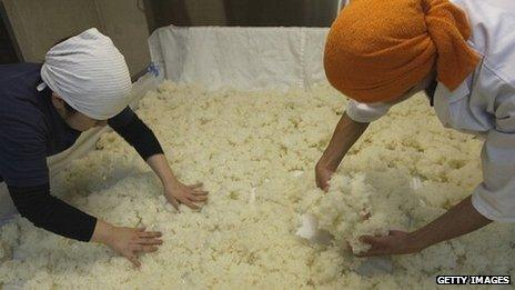 Steamed rice being spread out at a sake brewery in Japan