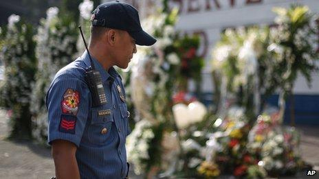 A Filipino policeman looks at flowers laid outside the gates of the Philippine National Police headquarters Camp Crame in suburban Quezon city, north of Manila, Philippines, Sunday, Feb. 1, 2015 for the 44 commandos who perished allegedly in a clash with Muslim rebels in Maguindanao, southern Philippines