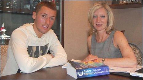 Footballer Raddy Majewski and English tutor Liz Nathan sit in the Nottingham Forest Football Club boardroom