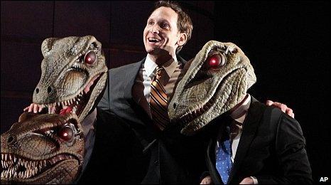 Stephen Kunken perform with actors wearing raptor masks in Enron