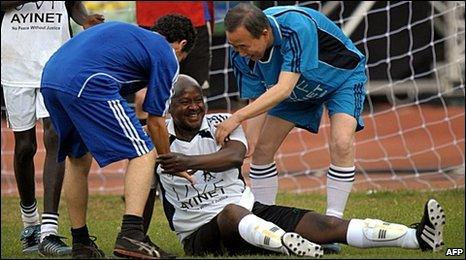 "Uganda""s President, Yoweri Museveni (C) is helped to his feet by UN Secretary General, Ban Ki-moon, during a football match in Kampala"