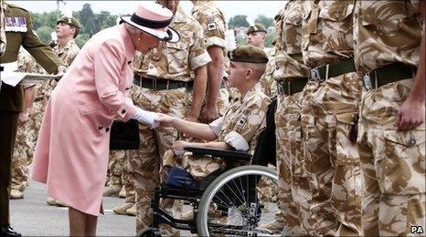 The Queen presents a medal to Fusilier Shaun Stocker at Chester Racecourse