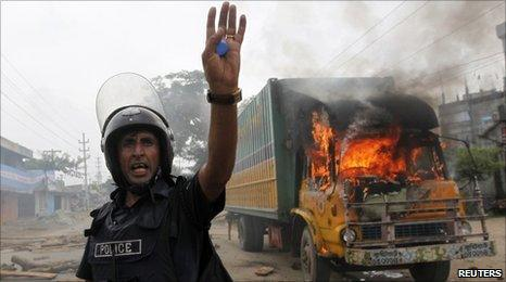 Policeman calls his comrades for help in front of a truck burnt by garment workers in Ashulia