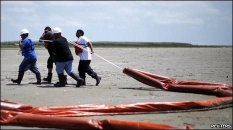 Workers remove oil booms from the beach in Louisiana