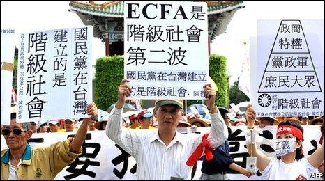 Taiwanese protesters hold up placards against trade pact