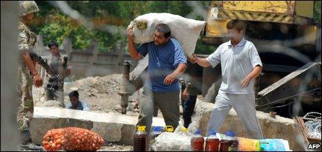 Two men carry provisions at the Kyrgyz-Uzbek border near a village of Nariman outside Osh on June 16, 2010