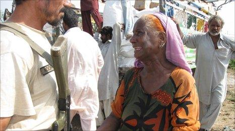 A woman pleads with a policeman to let her receive aid at a camp in Sukkur.