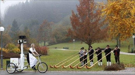 A woman on a Street View bike passes German musicians