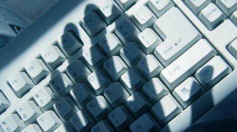 Hand in silhouette over a keyboard