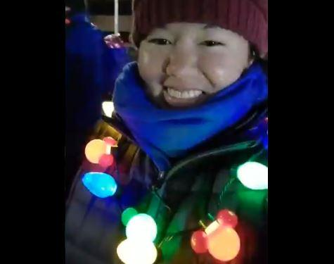 Patricia in her multicoloured flashing garland smiling to the camera