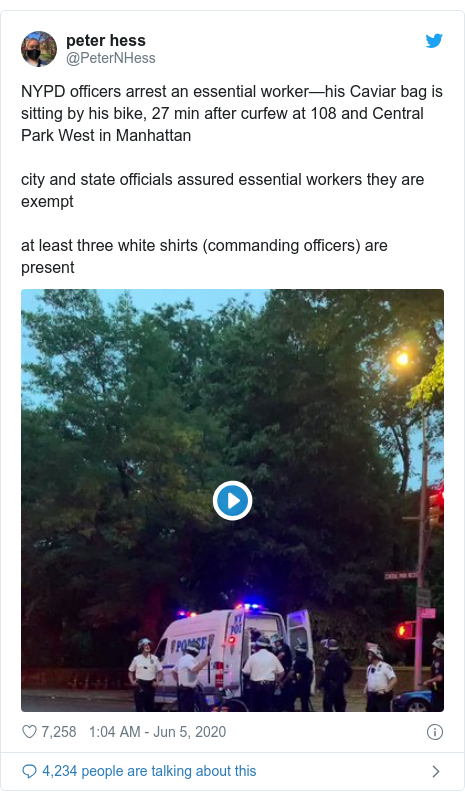 Twitter post by @PeterNHess: NYPD officers arrest an essential worker—his Caviar bag is sitting by his bike, 27 min after curfew at 108 and Central Park West in Manhattancity and state officials assured essential workers they are exemptat least three white shirts (commanding officers) are present