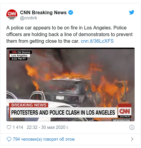 Twitter пост, автор: @cnnbrk: A police car appears to be on fire in Los Angeles. Police officers are holding back a line of demonstrators to prevent them from getting close to the car.
