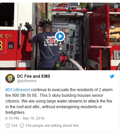 Twitter post by @dcfireems: #DCsBravest continue to evacuate the residents of 2 alarm fire 900 5th St SE. This 5 story building houses senior citizens. We are using large water streams to attack the fire in the roof and attic, without endangering residents or firefighters.