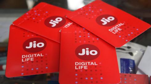 A shopkeeper displays JIO simcards at a mobile phone store in Mumbai on July 19, 2017.