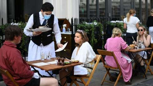 A waiter wearing a mask serves customers sat outside a restaurant in central London, back in September
