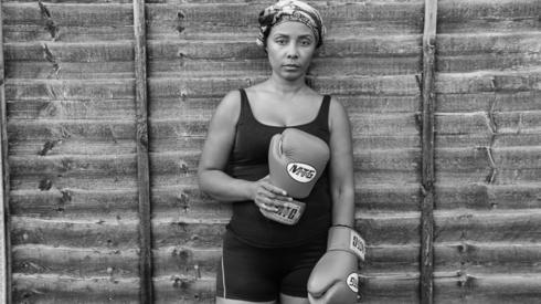 A woman poses against a wooden fence holding boxing gloves