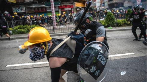 Protestor in Hong Kong being held back by police