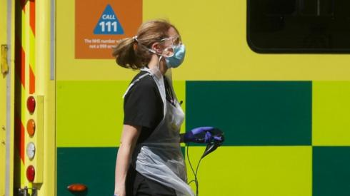 A medical worker walking in front of an ambulance