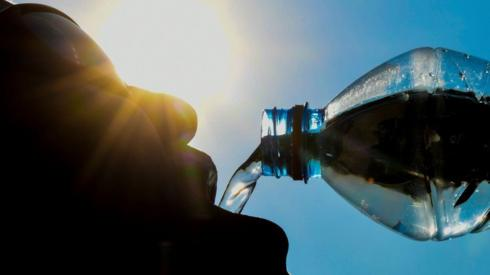 A man poses while drinking from a water bottle in the French city of Lille on 25 July, 2018