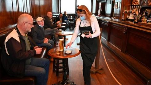 Bar worker in a pub with customers