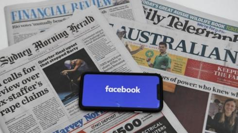 Phone screen with Facebook logo and Australian newspapers