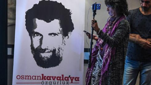 A journalist stands in front of a poster featuring jailed businessman and philanthropist Osman Kavala in October 2018