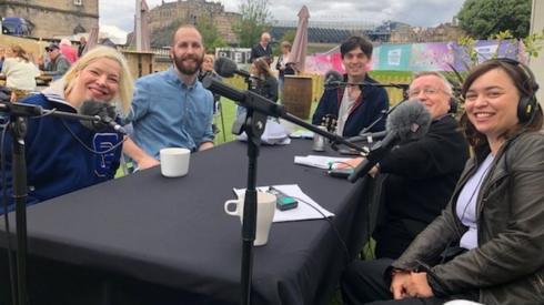 The podcast team at a table with microphones in Edinburgh