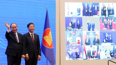 """Vietnam""""s Prime Minister Nguyen Xuan Phuc (L) and Minister of Industry and Trade Tran Tuan Anh (R) cheer after the virtual signing ceremony for the Regional Comprehensive Economic Partnership (RCEP) in Hanoi, Vietnam, 15 November 2020."""