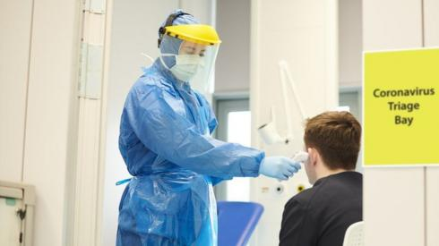 A nurse in protective wear taking a temperature