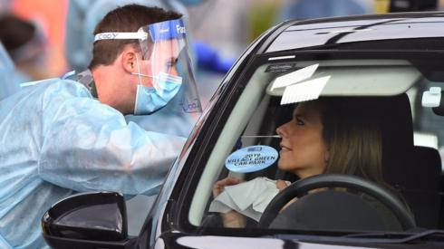 Health worker tests resident in Melbourne at drive-through site