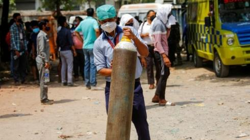 A healthcare worker holds an oxygen canister in Delhi
