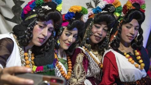 """Young Amazigh (Berber) women pose for a selfie photograph during the annual """"Engagement Moussem"""" festival near the village of Imilchil in central Morocco's high Atlas Mountains on September 21, 2019. Each year in the High Atlas Mountains hamlet of Ait Amer, tribes celebrate with dances and music, the collective wedding of young Amazigh couples during the traditional festival of """"Engagement Moussem"""