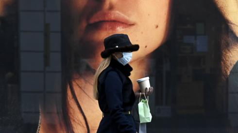 A woman wearing a protective mask walks past a store window in the city of Munich