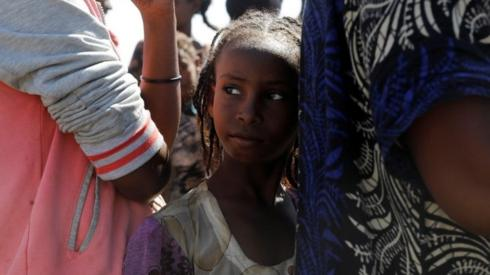 An Ethiopian girl stands in line to receive food, at a transit camp, which houses refugees fleeing the fighting in the Tigray region, on the border in Sudan