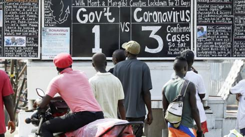 People reading a blackboard news board in Monrovia, Liberia - Monday 30 March 2020