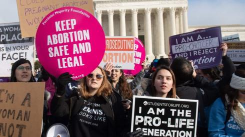 "Pro-choice activists hold signs alongside anti-abortion activists participating in the ""March for Life,"" an annual event to mark the anniversary of the 1973 Supreme Court case Roe v. Wade, which legalized abortion in the US, outside the US Supreme Court in Washington, DC"
