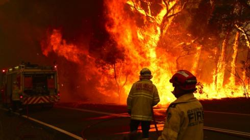 Two firefighters approach a blaze in New South Wales