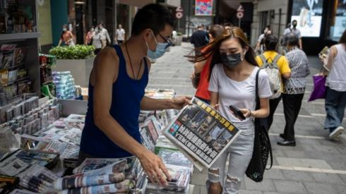 A woman buys a copy of Apple Daily newspaper at a news stand in Hong Kong, China, 18 June 2021.