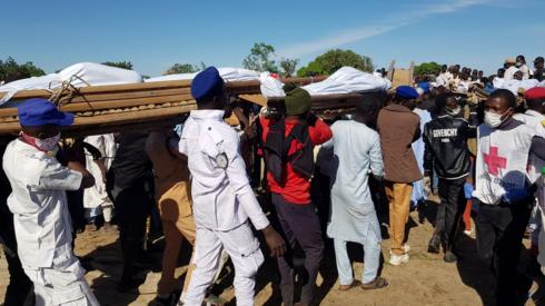 Men carry the bodies of people killed by militant attack, during a mass burial in Zabarmari, in the Jere local government area of Borno State, in northeast Nigeria, November 29, 2020.